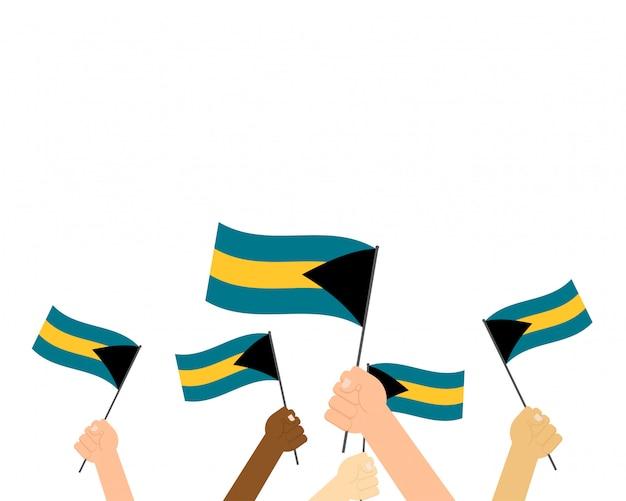 Mãos segurando bandeiras de bahamas