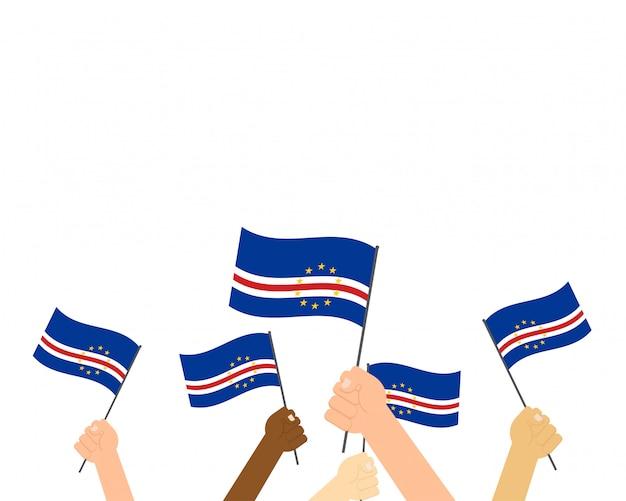 Mãos segurando bandeiras de cabo verde