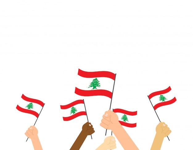 Mãos segurando bandeiras do líbano