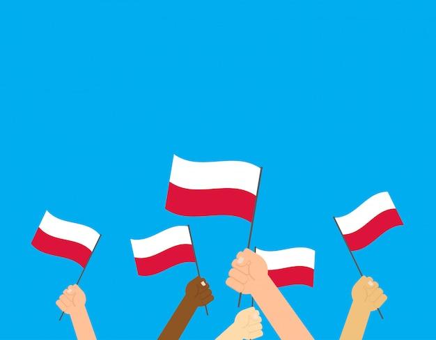 Mãos, segurando, polônia, bandeiras
