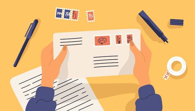 Mãos segurando um envelope com selos rodeados por artigos de papelaria.