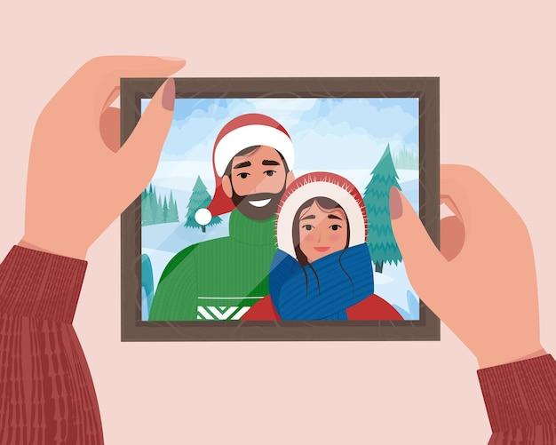 Mãos segurando um retrato de família de natal no quadro. foto para memória. ilustração em vetor plana fofa