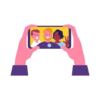 Mãos segurando um smartphone com uma selfie alegre de amigos na tela