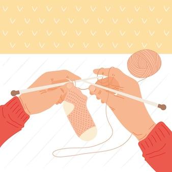 Mãos segurando uma meia de malha com fio