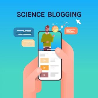 Mãos usando smartphone com astrônomo cientista blogger na tela homem dando treinamento educacional sobre sistema solar streaming ao vivo blogging conceito retrato on-line aplicativo móvel