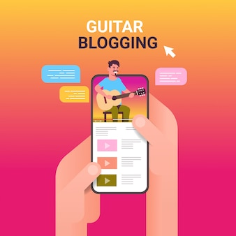 Mãos usando smartphone com blogueiro musical na tela homem tocando guitarra streaming ao vivo blogging conceito retrato app móvel on-line