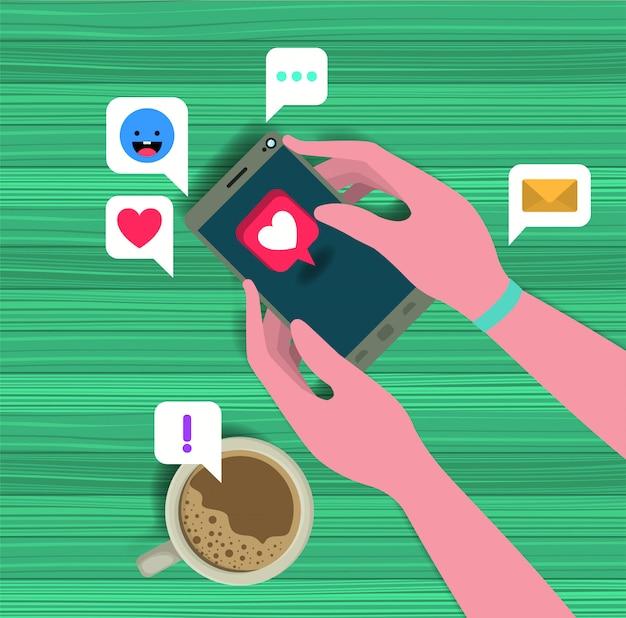 Mãos usando smartphone com xícara de café e ícones sociais