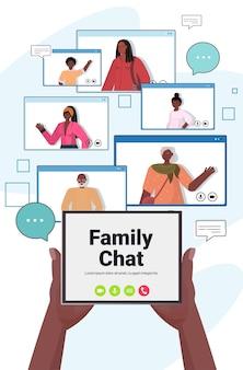 Mãos usando tablet pc conversando com pessoas afro-americanas nas janelas do navegador da web durante reunião virtual videochamada familiar chat conceito de comunicação online vertical