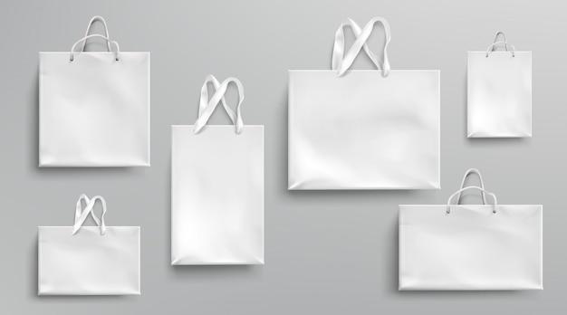 Maquete de sacolas de papel, pacotes brancos com alças de corda e laço, pacotes de presente ecológico retangular em branco, isolado mock up para branding e design de identidade corporativa, conjunto 3d realista
