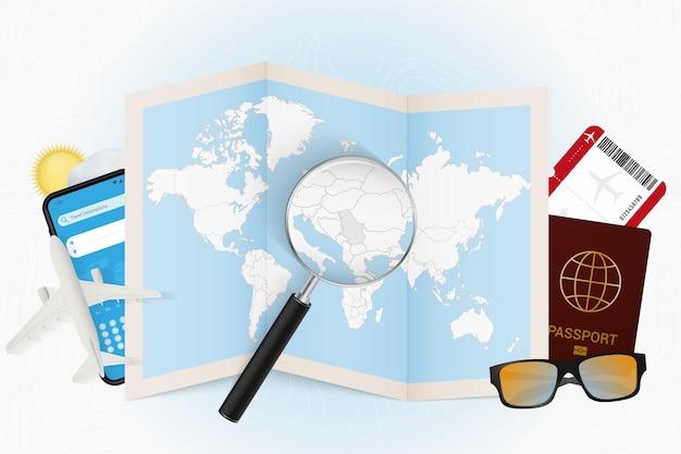 Maquete de turismo de destino de viagem na sérvia com equipamento de viagem e mapa-múndi com lupa