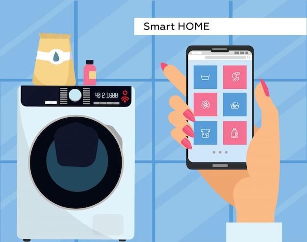 Máquina de lavar roupa controlada via smartphone com wi-fi. aplicativo de controle remoto para smartphone. feminino mão segura o celular com os botões na tela.