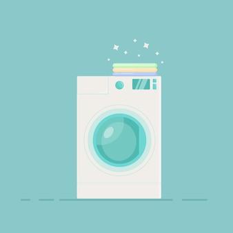 Máquina de lavar roupa em um fundo azul, roupa limpa encontra-se por cima. plano