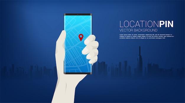 Marcador de pinos gps e celular na mão com o fundo da cidade. conceito de localização e instalação, tecnologia gps