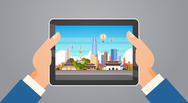 Marcos de viagens coreia mãos segurando digital tablet com paisagem de seul