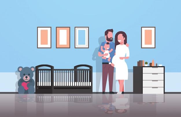 Marido com mulher grávida segurando o bebê recém-nascido em pé perto do berço