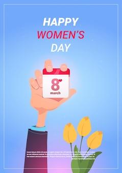 Masculino mão segurando a página de calendário com data de março de 8 de março sobre o modelo de fundo com tulipas feliz dia das mulheres ...