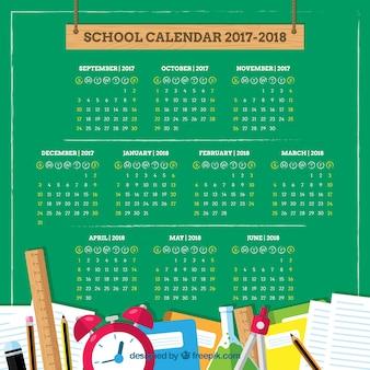Materiais escolares e calendário no quadro-negro