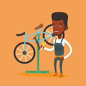 Mecânico de bicicleta africano trabalhando na oficina.