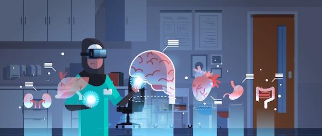 Médica árabe de óculos digitais, olhando para os órgãos de realidade virtual