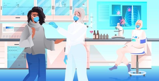 Médica usando máscara fazendo teste de esfregaço para amostra de coronavírus de paciente afro-americana para diagnóstico de pcr