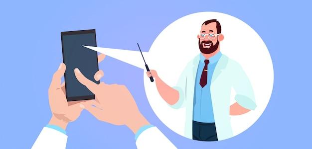 Medicina móvel app com a mão segurando o telefone inteligente sobre o médico do sexo masculino