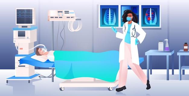 Médico afro-americano com máscara e traje de proteção examinando homem paciente na cama covid-19 pandemia