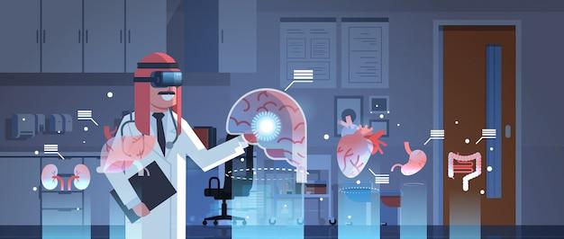 Médico árabe masculino, usando óculos digitais, olhando para os órgãos de realidade virtual