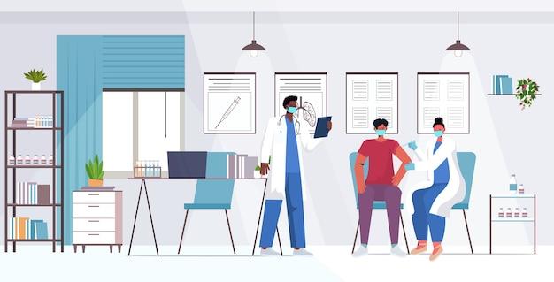 Médico com máscara vacinando paciente masculino luta contra coronavírus conceito de desenvolvimento de vacina hospital moderno escritório interior ilustração horizontal de corpo inteiro