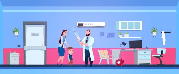 Médico de família, segurando a seringa no quarto do hospital com a mãe e filho pequeno