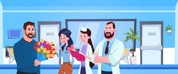 Médico e enfermeira dar recém-nascido para pais felizes no hospital