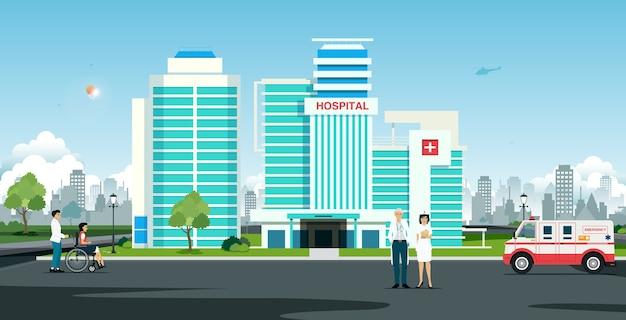 Médico e enfermeira em frente ao hospital com ambulância
