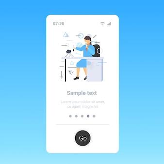 Médico feminino blogger segurando tubos de ensaio com líquidos diferentes cientista mulher gravando vídeo com a câmera no tripé medicina blogging conceito smartphone tela móvel app