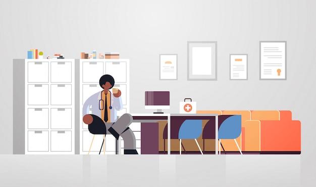 Médico masculino no jaleco branco tendo café medicina conceito médico americano africano trabalhador médico sentado no local de trabalho moderno hospital clínica escritório interior comprimento total horizontal