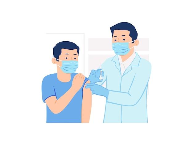 Médico masculino segurando uma seringa para dar injeção de vacina a um paciente do sexo masculino usando máscara médica.