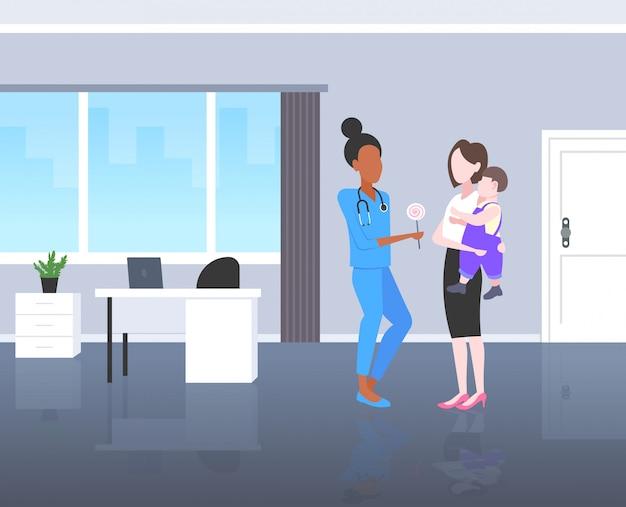 Médico pediatra dando pirulito para menino consulta conceito de saúde mãe segurando o bebê em suas mãos escritório moderno hospital interior comprimento total