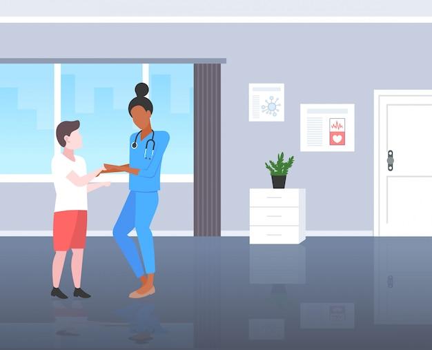 Médico pediatra menino paciente paciente mulher de uniforme examinar miúdo consulta médica conceito moderno departamento pediátrico hospital quarto interior comprimento total