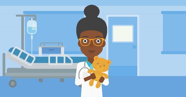Médico pediatra segurando o ursinho de pelúcia.