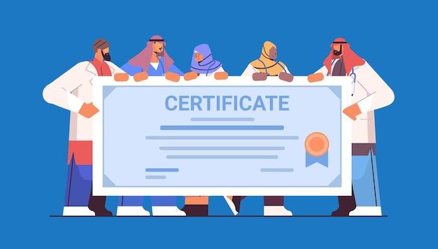 Médicos árabes formados com certificado de diplomados árabes celebrando diploma acadêmico educação médica em universidade