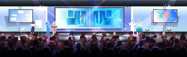 Médicos mascarados apresentando células de coronavírus na tribuna da conferência médica covid-19 conceito de pandemia