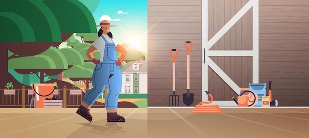 Menina agricultora de uniforme com ferramentas de jardim e fazenda, equipamento de jardinagem, perto de portas de celeiro de madeira, agricultura ecológica, ilustração de corpo inteiro horizontal