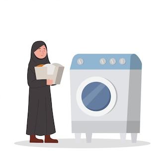 Menina árabe trazer a roupa para a máquina de lavar