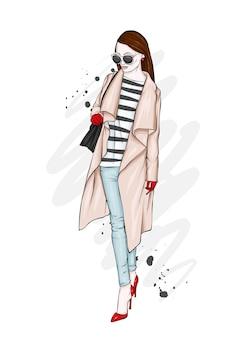 Menina bonita, alta e esbelta com um casaco, calças e óculos elegantes.