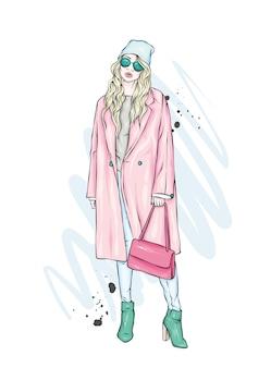 Menina bonita, alta e esguia em um elegante casaco, calças, óculos e chapéu.