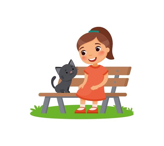 Menina bonitinha e gatinho preto estão sentados no banco