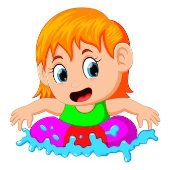 Menina bonitinha flutuando em um anel em uma piscina