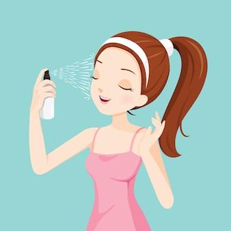 Menina borrifando água mineral no rosto