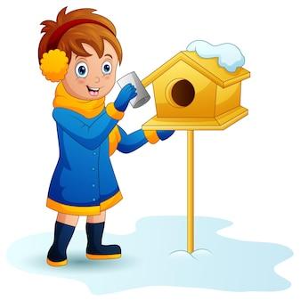 Menina coloca uma carta na caixa de correio no inverno