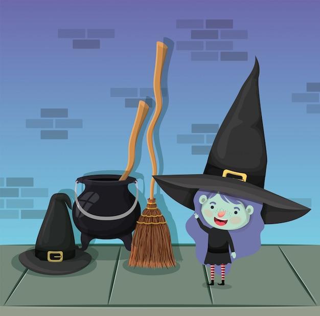 Menina com fantasia de bruxa e caldeirão e vassoura