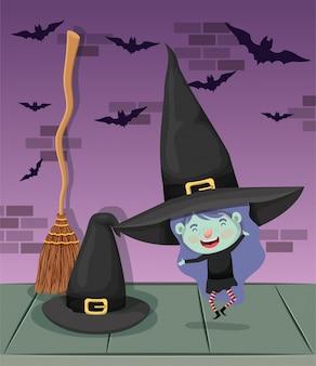 Menina com fantasia de bruxa na parede e vassoura