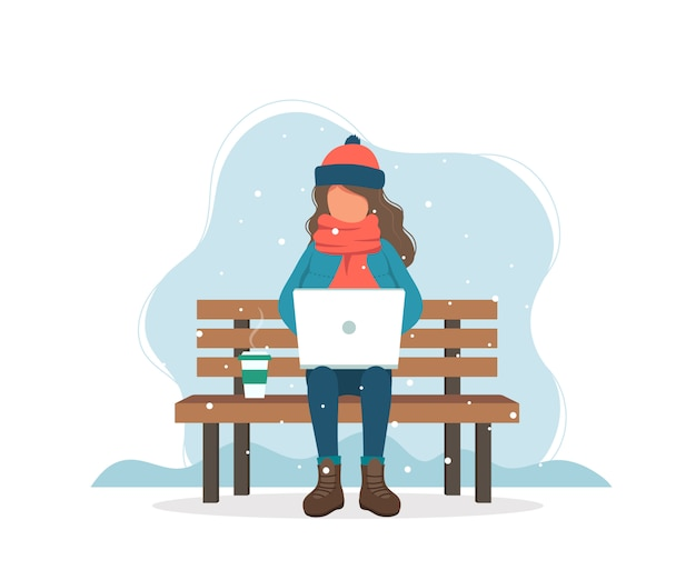 Menina com o computador no banco no inverno com café.